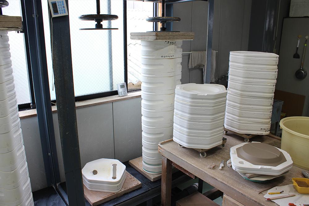 圧力鋳込み成形の写真_白い石膏型が縦に連なり、中に陶器用の泥を圧力で注入、右は型を開いて中の土が皿状に成形された様子