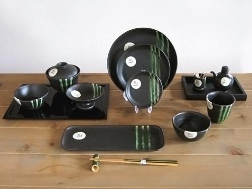 黒い皿に織部の緑のラインの入ったオリジナルの食器セット12種類、お茶碗、吸い物入れ足つき皿、丸皿サイズ3種、長皿、コップ、醤油入れ、爪楊枝入れ。木のお箸