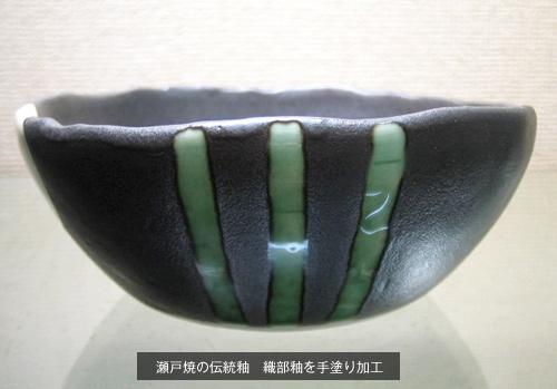 黒いお皿のアップ写真。3本線の装飾。瀬戸焼きの伝統釉薬の織部焼きを手塗り加工