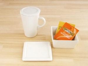 蓋付きのマグカップとティーカップトレイ、オレンジとイエローのパッケージのお茶がのっている。