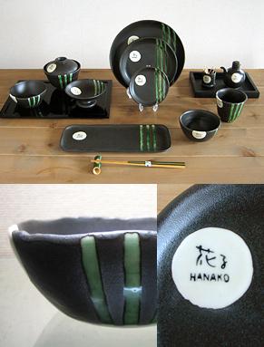 黒に緑のラインの入ったオリジナルの食器セット12種類、お茶碗、吸い物入れ足つき皿、丸皿サイズ3種、長皿、コップ、醤油入れ、爪楊枝入れ。ロゴのアップ写真。ラインのアップ写真